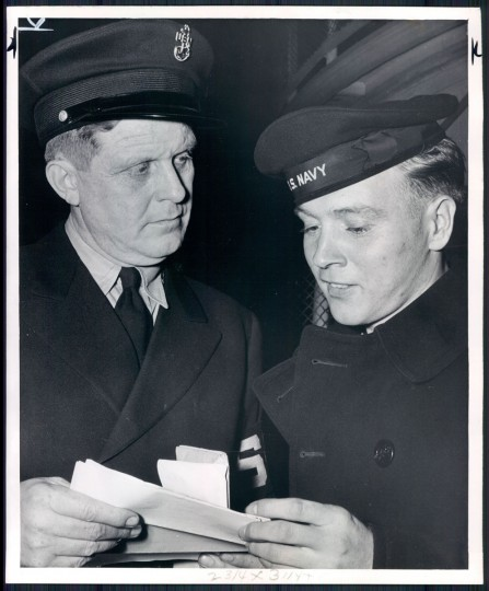 CPO Arlie C. Hager, who has been riding the Old bay line for four years for the Shore Patrol, examines the leave papers of Hawthorne Austin of Buchanan, Va. (Baltimore Sun archives, 1946)