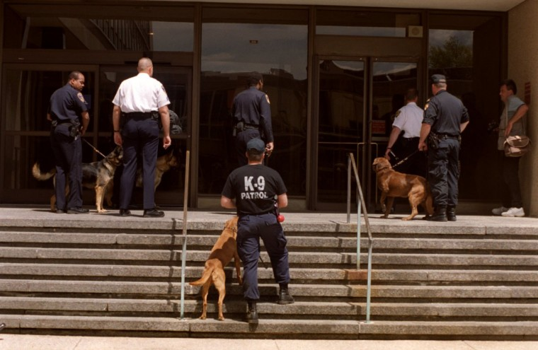 Bomb squad members and police k-9 units enter a state office building on Preston St. to investigate one of several area bomb threats. (Elizabeth Malby/Baltimore Sun, 1999)
