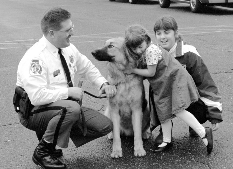 "Officer Robert Griffith of Baltimore County Police, lets his children Grethen, 5, and Whitney, 10, congratulate new K-9 officer, ""Brutus."" (Jed Kirschbaum/Baltimore Sun, 1996)"