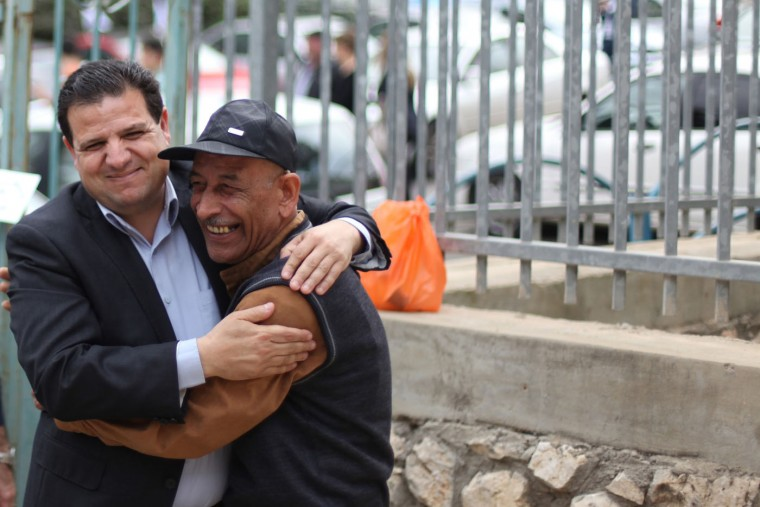 Ayman Odeh, left, chairman of the newly formed Joint List of Arab parties, embraces a supporter at a polling place in Nazareth on Tuesday, March 17, 2015. Arab citizens of Israel voted in record numbers Tuesday to propel the Joint List to the third-largest party in Knesset, Israel's parliament. (Daniella Cheslow/McClatchy/TNS)
