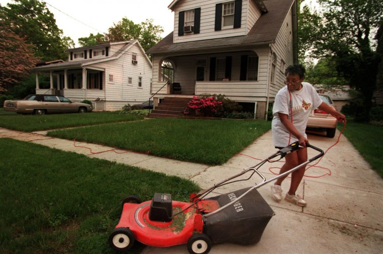 Gladys Savage, who has lived in the same house on Norwood Ave. for 35 years, took time out to mow her front lawn. Photo taken May 12, 1999. (Kenneth K. Lam/Baltimore Sun)
