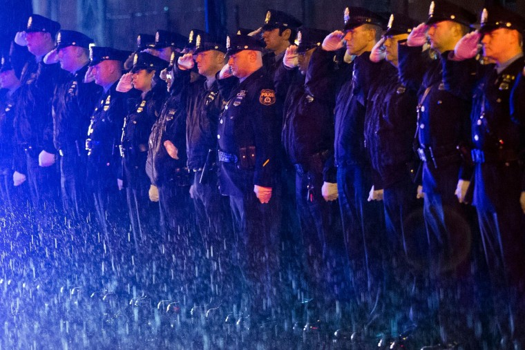 Law enforcement officers salute the arrival of the remains of Philadelphia Police Officer Robert Wilson III before a funeral procession in Philadelphia. City officials said on March 5, 2015 Wilson was shot and killed after he and his partner exchanged gunfire with two suspects trying to rob a video game store. (Matt Rourke/Associated Press)