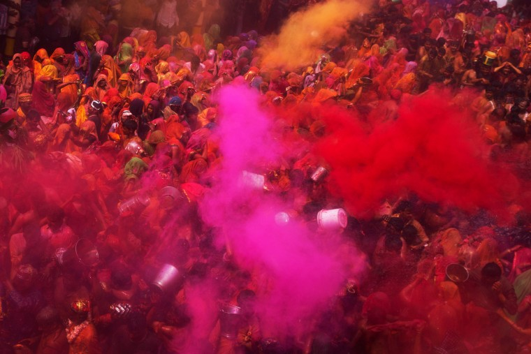 "Colored powder and water is thrown as Hindu devotees participate in ""Huranga,"" during celebrations marking Holi, the Hindu festival of colors, at the Baldev Temple in Dauji, 180 kilometers (113 miles) south of New Delhi, India. During Huranga women playfully hit men with cloth whips as men drench them with buckets of colored water. (Bernat Armangue/Associated Press)"