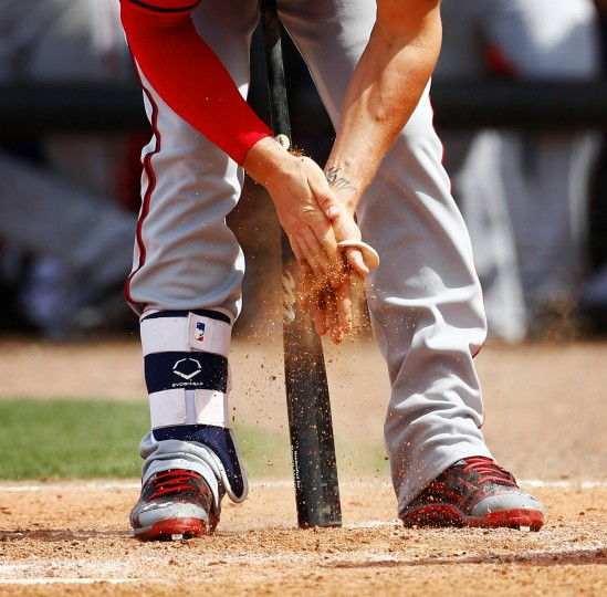 Washington Nationals left fielder Bryce Harper (34) rubs dirt on his hands a s get set to bat against the New York Mets in of an exhibition spring training baseball game in Port St. Lucie, Fla. (John Bazemore/Associated Press)