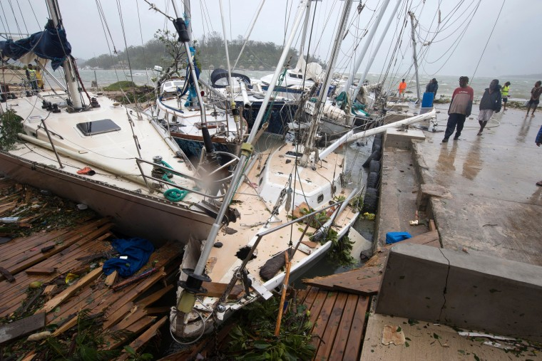 In this image provided by UNICEF Pacific, people on a dock view yachts damaged in Port Vila, Vanuatu, Saturday, March 14, 2015, in the aftermath of Cyclone Pam. Winds from the extremely powerful cyclone that blew through the Pacific's Vanuatu archipelago are beginning to subside, revealing widespread destruction. (UNICEF Pacific, Humans of Vanuatu/ via Associated Press)