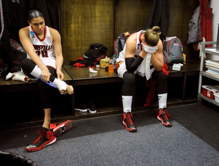 Louisville players Ariana Freeman, left, and Sara Hammond sit in the locker room following their 82-66 loss to Dayton in a women's college basketball regional semifinal game in the NCAA Tournament in Albany, N.Y. (Tim Roske/Associated Press)
