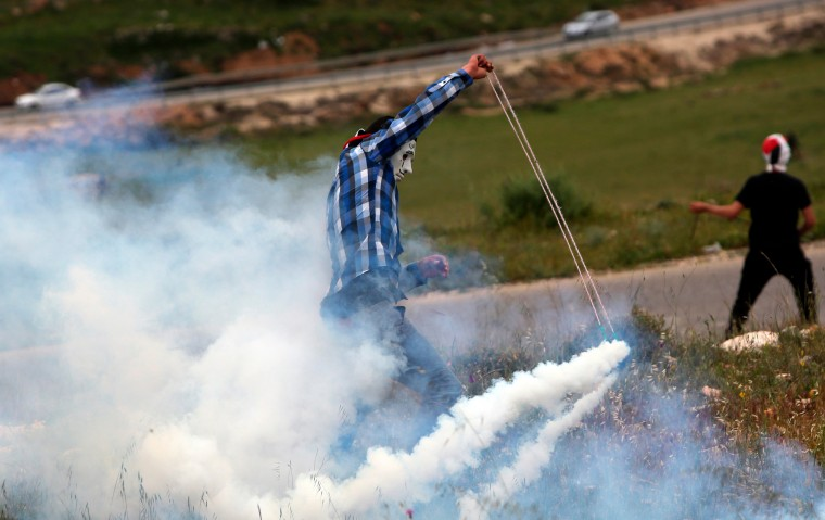 A Palestinian protester uses a slingshot to throw back a tear gas canister during clashes with Israeli security forces following a demonstration against Palestinian land confiscation to expand the nearby Jewish Hallamish settlement in the West Bank village of Nabi Saleh, located near Ramallah, two days ahead of the commemoration of Land Day. The annual Land Day demonstrations are held to remember six Arab Israeli protesters who were shot dead by Israeli police and troops during mass demonstrations in 1976 against plans to confiscate Arab land in the Galilee. (Abbas Momani/AFP-Getty Images)