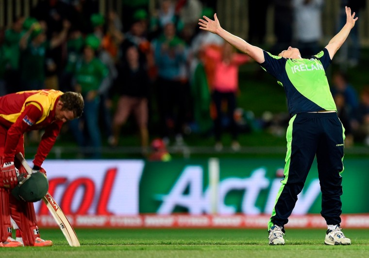 Ireland cricketer Kevin O'Brien reacts after taking the wicket of Zimbabwe batsman Sean Williams (L) at the Bellerive Oval ground during the 2015 Cricket World Cup Pool B match between Ireland and Zimbabwe in Hobart. (Indranil Mukherjee/AFP-Getty Images)