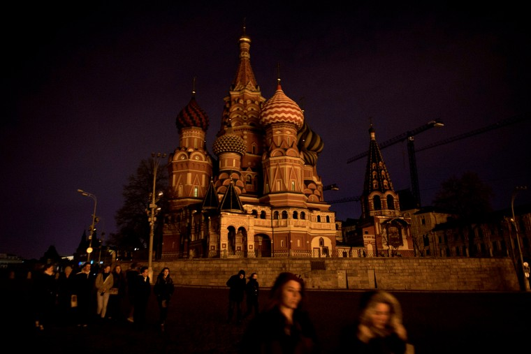 People walk past St. Basil's Cathedral with its lights off as part of the Earth Hour environmental campaign in central Moscow. (Alexander Utkin/AFP-Getty Images)