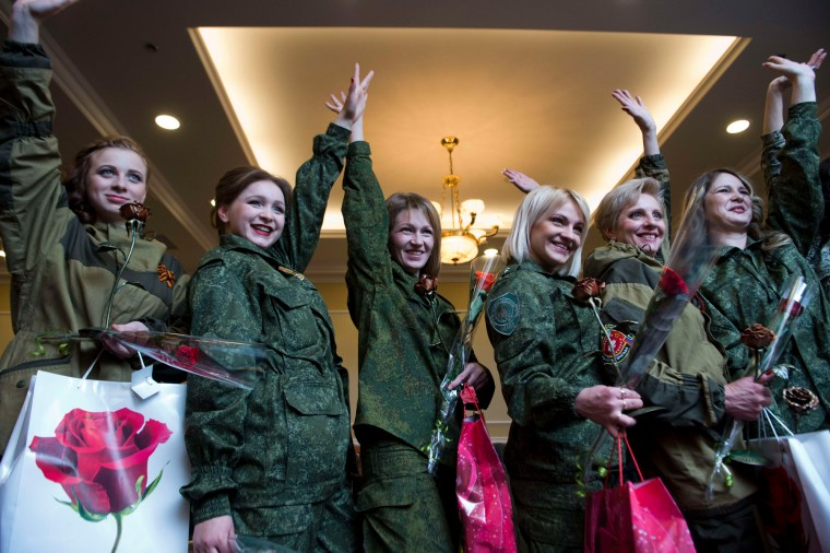 Women operating in combat battalions of the self-proclaimed People Republic of Donetsk (DNR) wave as they pose for photographers after taking part in a fashion show during a function in Donetsk. (John Macdougall/AFP-Getty Images)