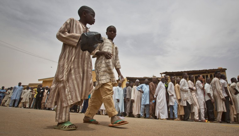 Two boys walk past a long line of men queuing while they face long delays to cast their vote in the afternoon at a polling station in Daura, the home town of opposition candidate Gen. Muhammadu Buhari, in northern Nigeria. Nigerians went to the polls Saturday in presidential elections which analysts say will be the most tightly contested in the history of Africa's richest nation and its largest democracy. (Ben Curtis/Associated Press)