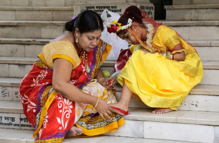 "A Hindu woman decorates the sole of her daughter's feet with vermillion for her to participate in a ceremony where young girls are worshipped as ""Kumari,"" or living goddess, during Ram Navami festival, at a temple in Kolkata, India. Ram Navami marks the birth of Hindu God Rama. (Bikas Das/Associated Press)"