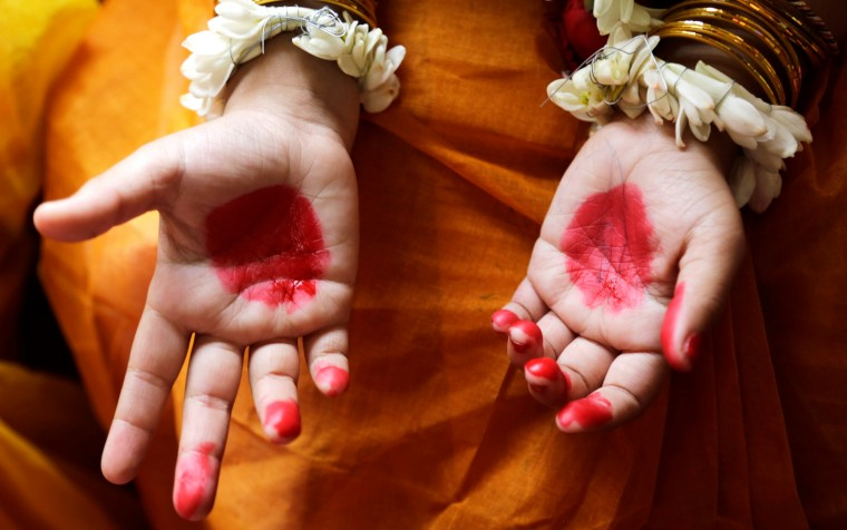 "A Hindu girl, her hands decorated with vermillion, participates in a ceremony where young girls are worshipped as ""Kumari,"" or living goddess, during Ram Navami festival, at a temple in Kolkata, India. Ram Navami marks the birth of Hindu God Rama. (Bikas Das/Associated Press)"