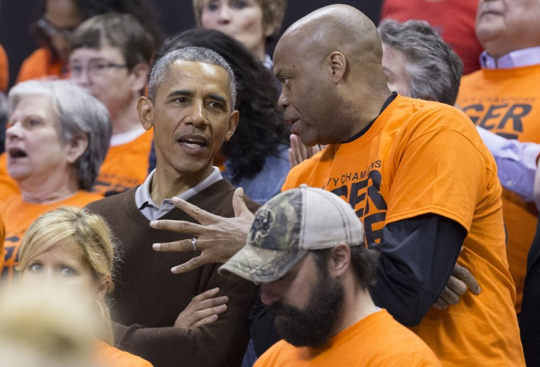U.S. President Barack Obama (L) sits beside his brother-in-law Craig Robinson while attending the Green Bay versus Princeton women's college basketball game in the first round of the NCAA tournament, March 21, 2015 in College Park, Maryland. President Barack Obama's niece Leslie Robinson plays for Princeton. (Photo by MIchael Reynolds-Pool/Getty Images)