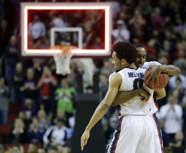 Gonzaga's Eric McClellan, right, hugs Silas Melson (0) at the buzzer as Gonzaga beat Iowa 87-68 in an NCAA tournament college basketball game in the Round of 32, Sunday, March 22, 2015, in Seattle. (AP Photo/Ted S. Warren)