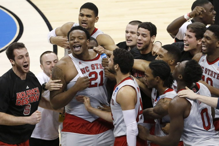 North Carolina State's Beejay Anya (21) celebrates with teammates after defeating LSU 66-65 in an NCAA tournament second round college basketball game Thursday, March 19, 2015, in Pittsburgh. (AP Photo/Gene J. Puskar)