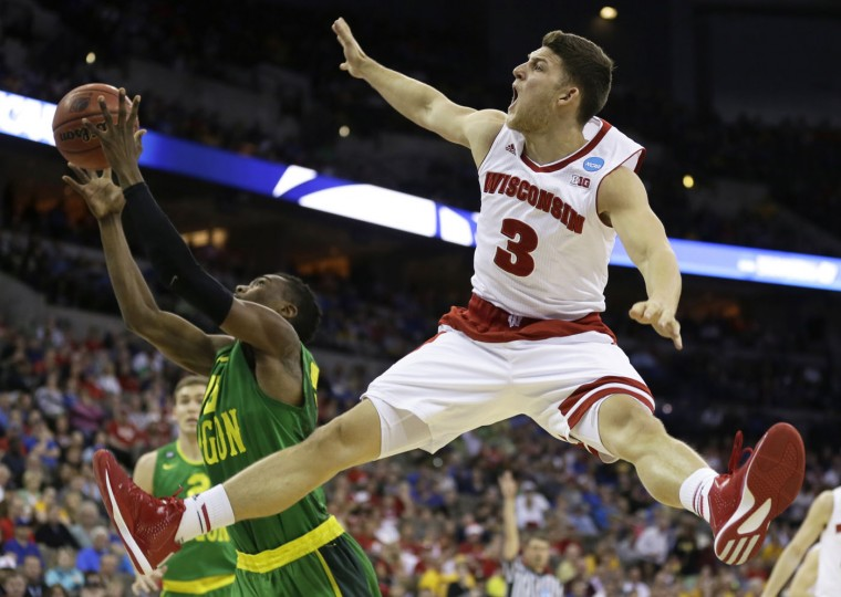Wisconsin's Zak Showalter (3) fights for a rebound with Oregon guard Jalil Abdul-Bassit, left, during the first half of an NCAA college basketball tournament Round of 32 game, Sunday, March 22, 2015, in Omaha, Neb. Abdul-Bassit was called for a foul on the play. (AP Photo/Charlie Neibergall)