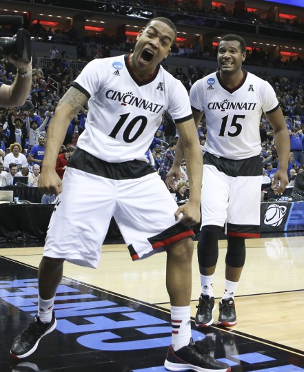 Cincinnati guard Troy Caupain, left, celebrates his game-tying basket against Purdue, forcing overtime, during an NCAA tournament second round college basketball game in Louisville, Ky., Thursday, March 19, 2015. At right is Cincinnati forward Jermaine Sanders. Cincinnati 66-65 in overtime. (AP Photo/David Stephenson)