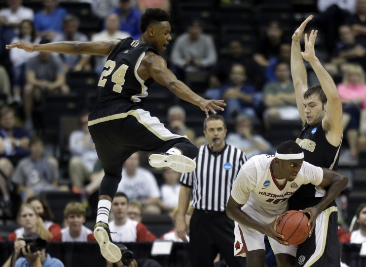 Wofford forward Justin Gordon (24) and teammate forward C.J. Neumann defend Arkansas forward Bobby Portis (10) during the second half of an NCAA tournament second round college basketball game Thursday, March 19, 2015, in Jacksonville, Fla. (AP Photo/John Raoux)