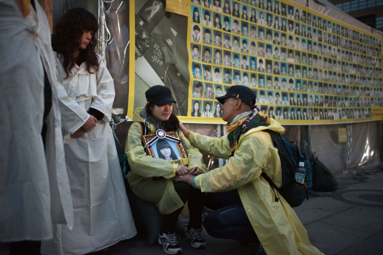 A relative of a victim of the Sewol ferry disaster is comforted as she sits before a poster showing photos of the victims, following a candle-light vigil in central Seoul on April 5, 2015. More than 600 people, including relatives of 250 high school students killed in the sinking, marched across Seoul for two days to protest what they say is the government's attempt to influence the investigation. The event was held ahead of the emotional first anniversary of the disaster, which left more than 300 dead or missing after the overloaded Sewol ferry sank off the country's southeast on April 16, 2014. Ed Jones/AFP Getty Images