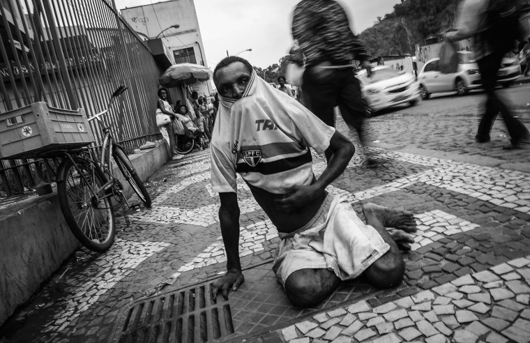 Vanderlei Correia, who is homeless, puts on his shirt while sitting in the Centro neighborhood on March 23, 2015 in Rio de Janeiro, Brazil. Correia said he lost his job as a bus cashier five years ago.
