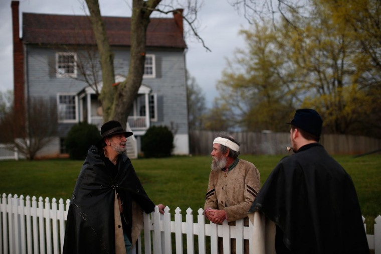 David Dunn (C), an American Civil War re-enactor assigned to the 26th North Carolina Infantry, talks with Union re-enactors David Bloom (L) and Jon Psotka (R) in front of the Peers House at the Appomattox Court House National Historical Park April 8, 2015 in Appomattox, Virginia. Tomorrow marks the 150th anniversary of Confederate General Robert E. Lee's surrender of the Army of Northern Virginia to Union forces commanded by General Ulysses S. Grant in the McLean House at Appomattox, Virginia. The surrender marked the beginning of the end of the American Civil War in 1865. (Photo by Win McNamee/Getty Images)