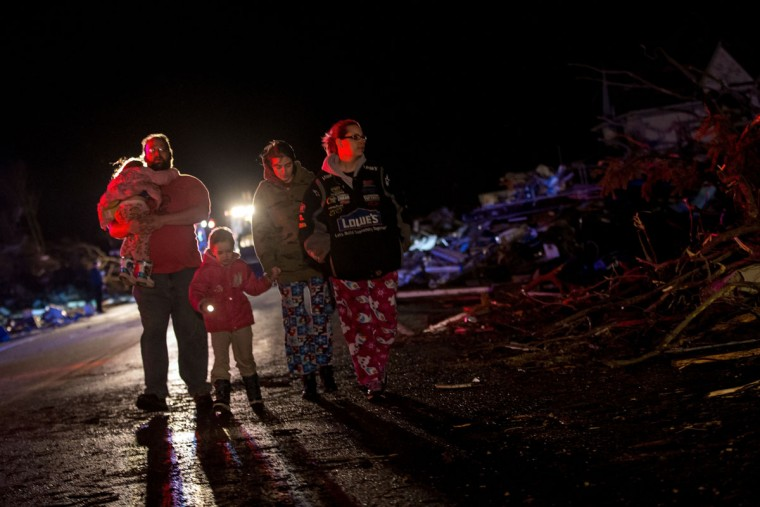 Stefanie and Matthew Hurley look at the wreckage on the IL-72 with their family after a tornado came through the town earlier in the day on April 9, 2015 in Fairdale, Illinois. According to reports, seven people were injured and one person was killed when tornadoes and thunderstorms passed through the northwestern suburbs of Chicago. (Photo by Jon Durr/Getty Images)