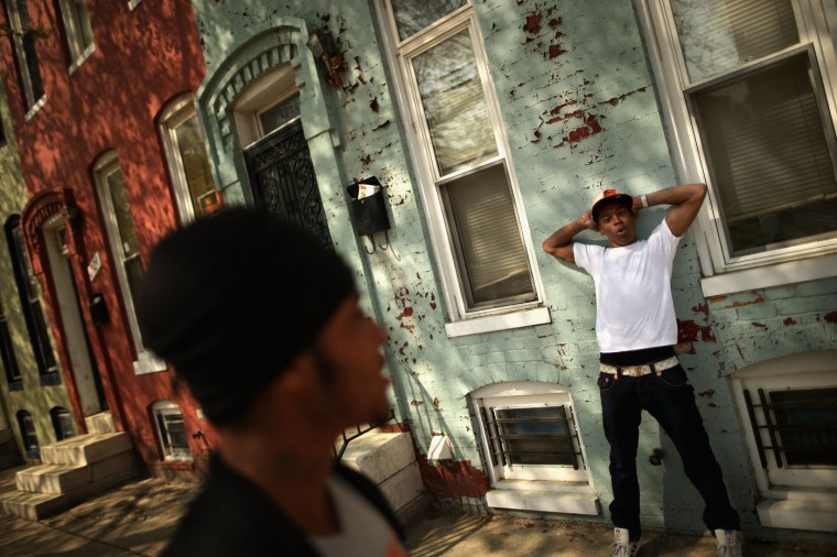 A young man who gave his name only as 'Mike' shows how police officers push young men in his Sandtown neighborhood against the wall before searching and questioning them April 21, 2015 in Baltimore, Maryland. Freddie Gray, a 25-year-old black man who lived in this neighborhood, was arrested for possessing a switch blade knife April 12 outside the Gilmor Homes housing project on Baltimore's west side. According to his attorney, Gray died a week later in the hospital from a severe spinal cord injury he received while in police custody. (Photo by Chip Somodevilla/Getty Images)