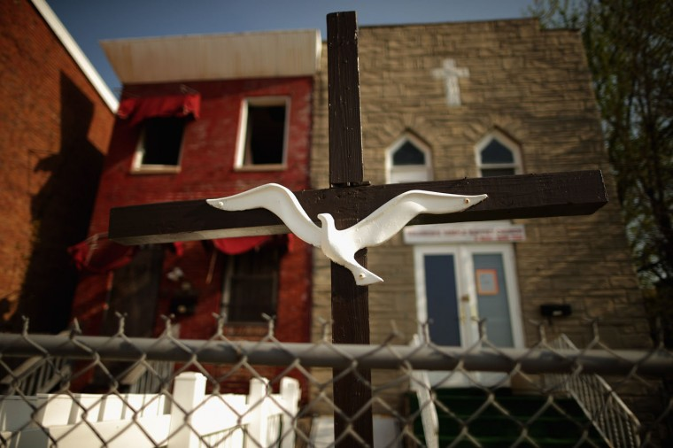 A Christian cross and dove mark the entrance to a small church near the place where Freddie Gray was arrested in the Sandtown neighborhood April 21, 2015 in Baltimore, Maryland. Gray, whose nickname was Pepper, was a 25-year-old black man who lived in this neighborhood and was arrested for possessing a switch blade knife April 12 outside the Gilmor Homes housing project on Baltimore's west side. According to his attorney, Gray died a week later in the hospital from a severe spinal cord injury he received while in police custody. (Photo by Chip Somodevilla/Getty Images)