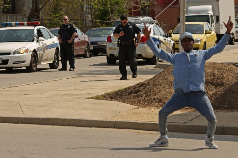 A young man taunts police officers and calls for revenge for the death of Freddie Gray as they respond to an emergency call in the Sandtown neighborhood April 21, 2015 in Baltimore, Maryland. Gray, a 25-year-old black man who lived in this neighborhood, was arrested for possessing a switch blade knife April 12 outside the Gilmor Homes housing project on Baltimore's west side. According to his attorney, Gray died a week later in the hospital from a severe spinal cord injury he received while in police custody. (Photo by Chip Somodevilla/Getty Images)