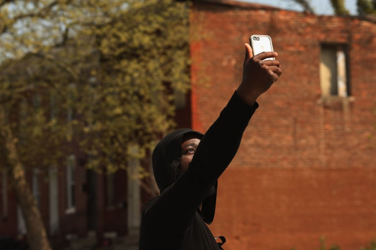 A young man who game his name only as Raheem video chats with a friend near the place where Freddie Gray was arrested in the Sandtown neighborhood April 21, 2015 in Baltimore, Maryland. Gray, whose nickname was Pepper, was a 25-year-old black man who lived in this neighborhood and was arrested for possessing a switch blade knife April 12 outside the Gilmor Homes housing project on Baltimore's west side. According to his attorney, Gray died a week later in the hospital from a severe spinal cord injury he received while in police custody. (Photo by Chip Somodevilla/Getty Images)