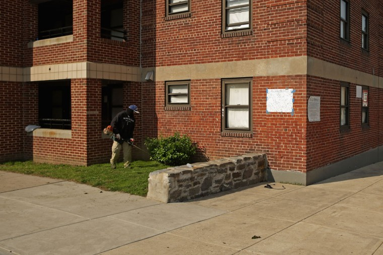 A man trims the grass near the spot where Freddie Gray was arrested outside the Gilmore Homes housing project in the Sandtown neighborhood April 21, 2015 in Baltimore, Maryland. Gray, a 25-year-old black man who lived in the neighborhood, was arrested for possessing a switch blade knife April 12 outside this building on Baltimore's west side. According to his attorney, Gray died a week later in the hospital from a severe spinal cord injury he received while in police custody. (Photo by Chip Somodevilla/Getty Images)