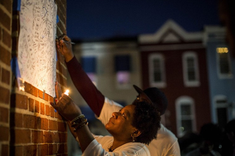 Baltimore resident Priscilla Jackson signs a memorial following a demonstration over the death of Freddie Gray, April 21, 2015 in Baltimore, Maryland. Gray, 25, died from spinal injuries on April 19, one week after being taken into police custody. (Photo by Drew Angerer/Getty Images)