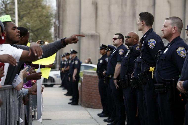 Baltimore Police Department officers stand behind a barrier while protestors gather near the Baltimore Police Department's Western District police station during a march and vigil over the death of Freddie Gray, April 21, 2015 in Baltimore, Maryland. Gray, 25, died from spinal injuries on April 19, one week after being taken into police custody. (Photo by Drew Angerer/Getty Images)