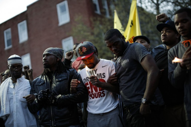 Protestors participate in a vigil for Freddie Gray down the street from the Baltimore Police Department's Western District police station April 21, 2015 in Baltimore, Maryland. Gray, 25, died from spinal injuries on April 19, one week after being taken into police custody. (Photo by Drew Angerer/Getty Images)