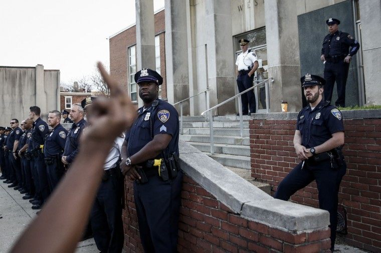 A protestor gestures toward police during a rally after a march for Freddie Gray that ended in front of the Baltimore Police Department's Western District police station, April 21, 2015 in Baltimore, Maryland. Gray, 25, died from spinal injuries on April 19, one week after being taken into police custody. (Photo by Drew Angerer/Getty Images)