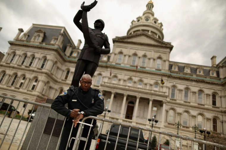 A Baltimore Police officer secures metal barricades in front of City Hall in anticipation of protests against police brutality and the death of Freddie Gray April 22, 2015 in Baltimore, Maryland. Gray, 25, was arrested by Baltimore Police for possessing a switch blade knife April 12 outside the Gilmor Homes housing project on Baltimore's west side. According to his attorney, Gray died a week later in the hospital from a severe spinal cord injury he received while in police custody. (Photo by Chip Somodevilla/Getty Images)