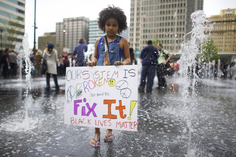 Micaiah Bakues-Freeman, 9, joins protestors demonstrating over the death of Freddy Gray outside City Hall on April 30, 2015 in Philadelphia, Pennsylvania. Freddie Gray, 25, was arrested for possessing a switch blade knife April 12 outside the Gilmor Houses housing project on Baltimore's west side. According to his attorney, Gray died a week later in the hospital from a severe spinal cord injury he received while in police custody. (Photo by Mark Makela/Getty Images)
