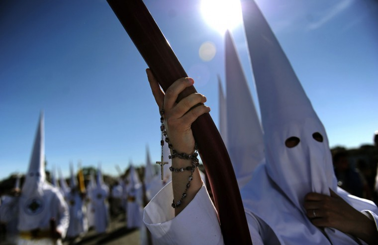 Penitent with a rosary on his hand parades during the San Gonzalo brotherhood procession in Sevilla on March 30, 2015. Christian believers around the world mark the Holy Week of Easter in celebration of the crucifixion and resurrection of Jesus Christ. (AFP Photo/Cristina Quicler)