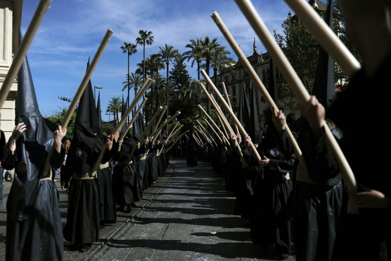 "Hooded members of the ""Los Estudiantes"" brotherhood hold candles during an Easter procession in Sevilla on March 31, 2015. Christian believers around the world mark the Holy Week of Easter in celebration of the crucifixion and resurrection of Jesus Christ. (AFP Photo/Cristina Quicler)"