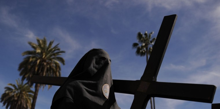 "A hooded member of the ""Los Estudiantes"" brotherhood holds a cross during an Easter procession in Sevilla on March 31, 2015. Christian believers around the world mark the Holy Week of Easter in celebration of the crucifixion and resurrection of Jesus Christ. (AFP Photo/Cristina Quicler)"