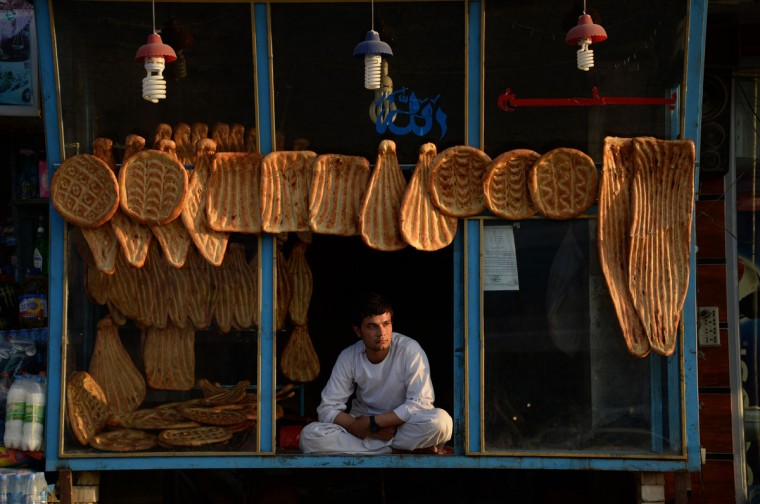 Afghan vendor Samim, 23, sits at his bakery as he waits to sell bread in Mazar-i-sharif on April 5, 2015. (AFP Photo/Farshad Usyan)