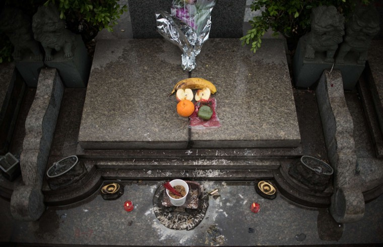 "Offerings lie on a grave during the annual ""Qingming"" festival, or Tomb Sweeping Day, at a public cemetery in Shanghai on April 6, 2015. During ""Qingming"" Chinese traditionally tend the graves of their departed loved ones and often burn paper money, model houses, cars, mobile phones and other goods as offerings to honour them and keep them comfortable in the afterlife. (AFP Photo/Johannes Eisele)"