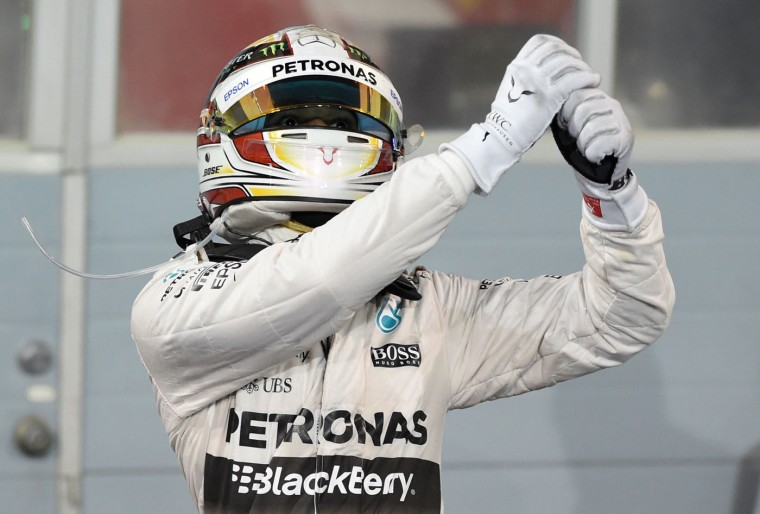 Mercedes AMG Petronas British driver Lewis Hamilton gestures towards to his teammates as he arrives in the winners enclosure after winning the Formula One Bahrain Grand Prix at the Sakhir circuit in the desert south of the Bahraini capital, Manama, on April 19, 2015. (Fayez Nureldine/AFP/Getty Images)