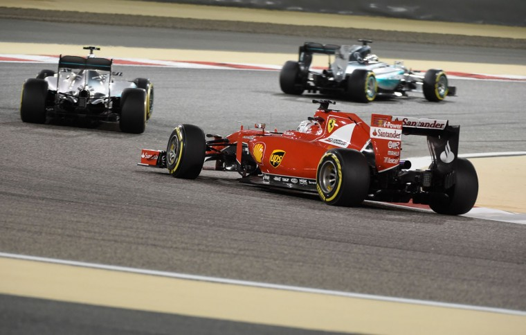 Scuderia Ferrari German driver Sebastian Vettel (front) races behind Mercedes AMG Petronas British driver Lewis Hamilton (top) and Mercedes AMG Petronas German driver Nico Rosberg during the Formula One Bahrain Grand Prix at the Sakhir circuit in the desert south of the Bahraini capital, Manama, on April 19, 2015. (Fayez Nureldine/AFP/Getty Images)