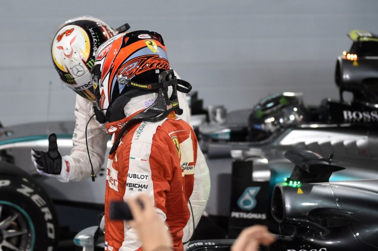 Mechanics check Mercedes AMG Petronas British driver Lewis Hamilton (C) shakes hands with Scuderia Ferrari Finnish driver Kimi Raikkonen (front) after winning the Formula One Bahrain Grand Prix at the Sakhir circuit in the desert south of the Bahraini capital, Manama, on April 19, 2015. (Fayez Nureldine/AFP/Getty Images)