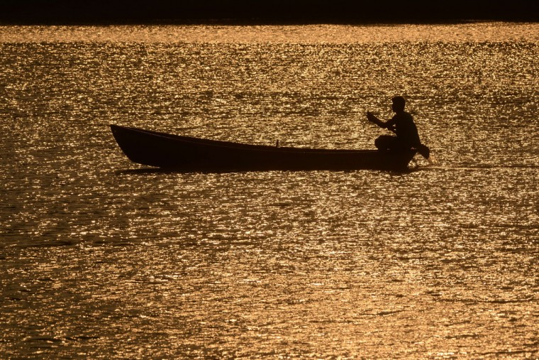 The silhouette of a fisherman is seen at sunset in the waters of Lake Suchitlan in Suchitoto, 47 km east of San Salvador, El Salvador on April 19, 2015. (AFP Photo/Marvin Recinos)