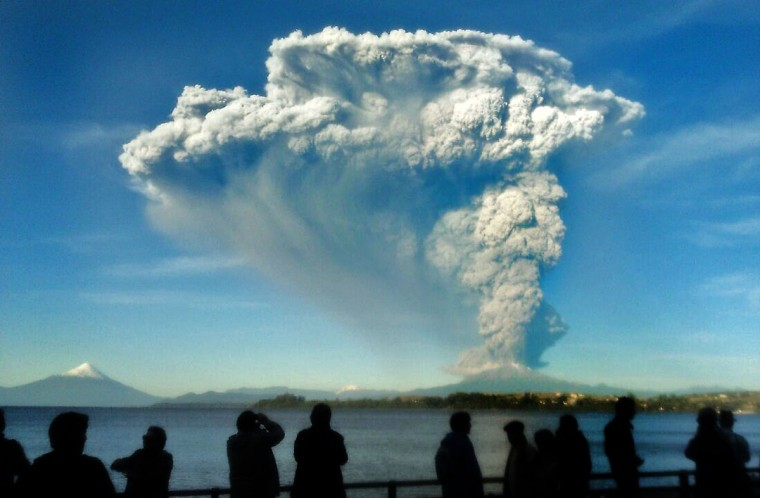 People watch from Puerto Varas, southern Chile, a high column of ash and lava spewing from the Calbuco volcano, on April 22, 2015. Chile's Calbuco volcano erupted on Wednesday, spewing a giant funnel of ash high into the sky near the southern port city of Puerto Montt and triggering a red alert. Authorities ordered an evacuation for a 10-kilometer (six-mile) radius around the volcano, which is the second in southern Chile to have a substantial eruption since March 3, when the Villarrica volcano emitted a brief but fiery burst of ash and lava. (AFP Photo/P /giordana )