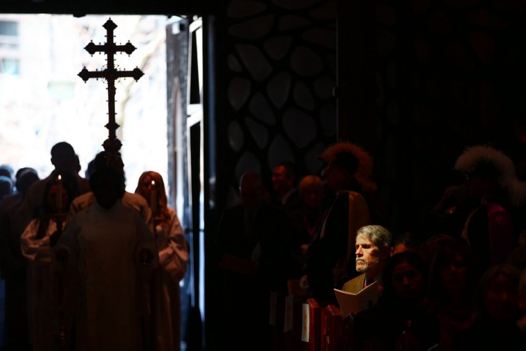 Light shines on a mourner as bishops process into Holy Name Cathedral for the funeral Mass of Cardinal Francis George on Thursday, April 23, 2015 in Chicago. George died last Friday at age 78 after a long battle with cancer. (Chris Walker/Chicago Tribune via AP, Pool)