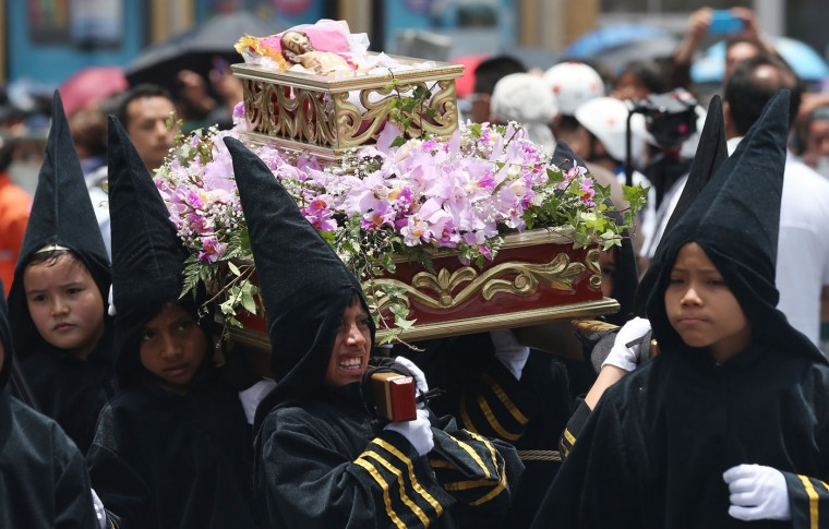Young boys dressed as penitents carry the religious float representing the 14th station of the cross, when the body of Jesus is placed in a tomb, in the Children's Holy Thursday Procession, in Tunja, Colombia, Thursday, April 2, 2015. In this annual Holy Week tradition, now in its 55th year, children carry religious floats and depict the key moments of the passion, death and resurrection of Jesus Christ. (AP Photo/Fernando Vergara)